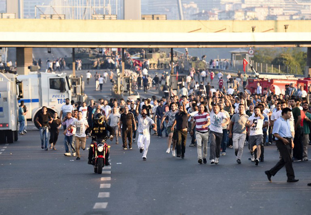 """People run away from tanks after taking over military position on the Bosphorus bridge in Istanbul on July 16, 2016, following an attempt by discontented soldiers to seize power from President Recep Tayyip Erdogan that claimed more than 250 lives. After the bloodiest challenge to his 13-year autocratic rule, Erdogan urged his backers to stay on the streets to prevent a possible """"flare-up"""" of yesterday's chaos in the strategic NATO member of 80 million people. / AFP PHOTO / BULENT KILIC"""