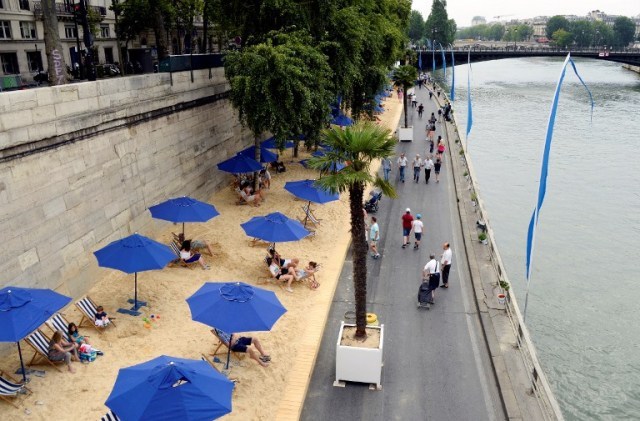 "A picture taken on the bank of the Seine river, in central Paris, on July 20, 2016 shows people relaxing under parasols in ""Paris Plage"" (Paris Beach) during the opening day of the event. The 15th edition of Paris Plage will run until September 4, 2016. / AFP PHOTO / BERTRAND GUAY"
