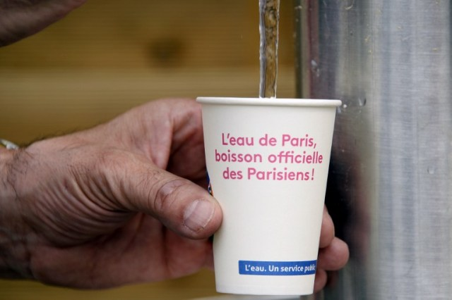 "A picture taken in central Paris, on July 20, 2016 in Paris Plage (Paris Beach) shows a man taking water in a cup reading ""Paris water, the Parisians official drink"". The 15th edition of Paris Plage will run until September 4, 2016. / AFP PHOTO / BERTRAND GUAY"