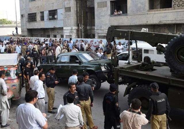 Una grúa levanta un vehículo del ejército en el sitio de un ataque de hombres armados en Karachi el 26 de julio de 2016. Dos soldados paquistaníes fueron asesinados a tiros el 26 de julio, cuando dos hombres armados en una motocicleta abrieron fuego contra su camioneta pick-up en la ciudad meridional de Karachi, dijeron las autoridades. AFP PHOTO / ASIF HASSAN