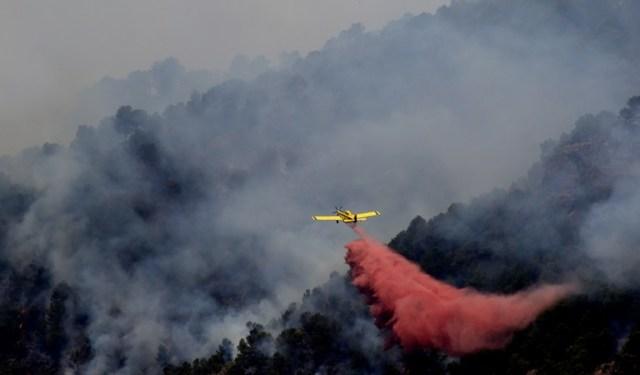 Un avión de combate de incendios forestales en una quema de Artana, cerca de Castellón, el este de España, el 26 de julio de 2016. Un incendio forestal, aún activa en más de 1.000 hectáreas en la región de Valencia (este de España), golpeó un parque natural y hecho que el ejército intervenir, según las autoridades regionales en la actualidad. JOSE JORDAN / AFP