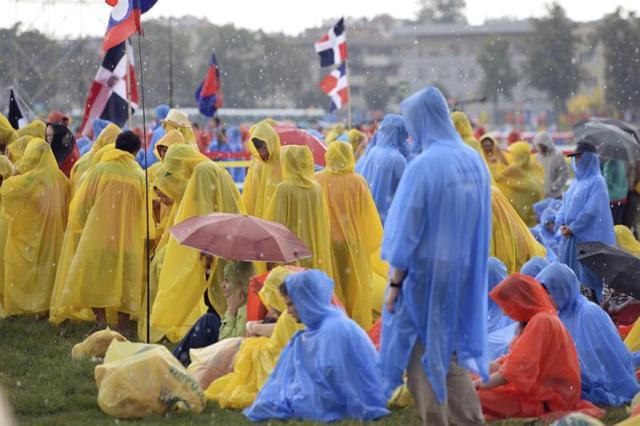 Varios peregrinos esperan bajo la lluvia para la misa inaugural de la XXXI Jornada Mundial de la Juventud (JMJ) en Cracovia, Polonia, hoy 26 de julio de 2016. La nueva edición de la Jornada Mundial de la Juventud comienza hoy y finaliza el próximo 31 de julio. El papa Francisco viaja desde el 27 al 31 de julio a Polonia para asistir a la JMJ y visitará los lugares símbolos de Juan Pablo II y recordará el Holocausto con un recorrido en silencio por los campos de Auschwitz y Bikernau. EFE/Maciej Kulczynsk