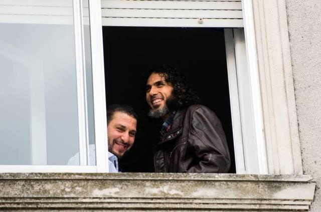 Foto de 5 de junio de 2015, Abu Wa'el Dhiab, de Siria, a la derecha, y Adel bin Muhammad El Ouerghi, de Túnez, ambos liberados los detenidos de Guantánamo, de pie junto a la ventana de su hogar compartido en Montevideo, Uruguay. Matilde Campodónico AP