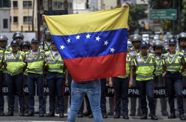 Un miembro de la oposición de la Venezuela representa una bandera nacional frente a policías nacionales durante una manifestación en Caracas el 27 de julio de 2016. La oposición de Venezuela llamó a protestas el miércoles para exigir las autoridades electorales permiten un referéndum sobre la eliminación de presidente, Nicolás Maduro, del poder. AFP PHOTO / JUAN BARRETO