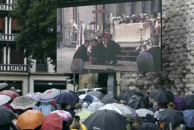 Mourners gather in the rain near a giant screen outside the Cathedral in Rouen, France, during a funeral service in memory of slain French parish priest Father Jacques Hamel at the Cathedral in Rouen, France, August 2, 2016.  Father Jacques Hamel was killed last week in an attack on a church at Saint-Etienne-du-Rouvray near Rouen that was carried out by assailants linked to Islamic State.   REUTERS/Jacky Naegelen