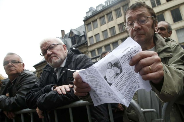 A mourner holds a leaflet with a picture of slain French parish priest Father Jacques Hamel durng a funeral ceremony at the Cathedral in Rouen, France, August 2, 2016.  Father Jacques Hamel was killed last week in an attack on a church at Saint-Etienne-du-Rouvray near Rouen that was carried out by assailants linked to Islamic State. REUTERS/Jacky Naegelen