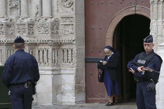 Armed French police stand guard as a nun leaves the Cathedral in Rouen after a funeral service in memory of slain French parish priest Father Jacques Hamel in Rouen, France, August 2, 2016.  Father Jacques Hamel was killed last week in an attack on a church at Saint-Etienne-du-Rouvray near Rouen that was carried out by assailants linked to Islamic State.   REUTERS/Jacky Naegelen