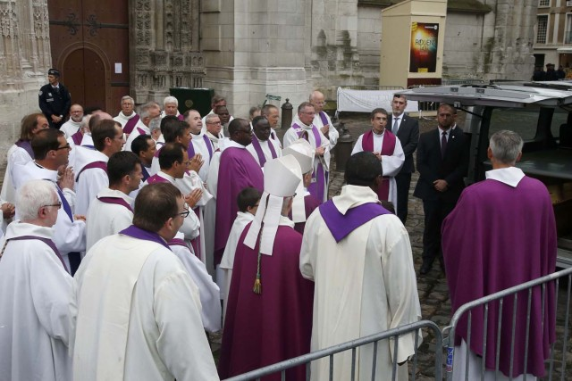 Religious leaders and priests gather near the hearse carrying the coffin of slain French parish priest Father Jacques Hamel after a funeral ceremony at the Cathedral in Rouen, France, August 2, 2016.  Father Jacques Hamel was killed last week in an attack on a church at Saint-Etienne-du-Rouvray near Rouen that was carried out by assailants linked to Islamic State.     REUTERS/Jacky Naegelen