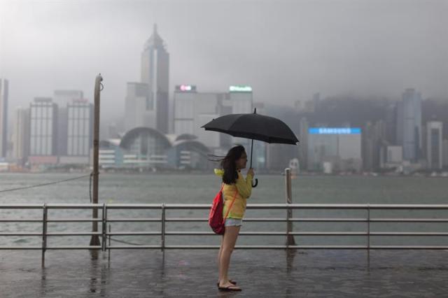 Una mujer observa desde el puerto Victoria afectado por los fuertes vientos del tifón Nida hoy, martes 2 de agosto de 2016, en Hong Kong (China). Nida es el primer gran tifón que golpea Hong Kong este año. EFE/JEROME FAVRE