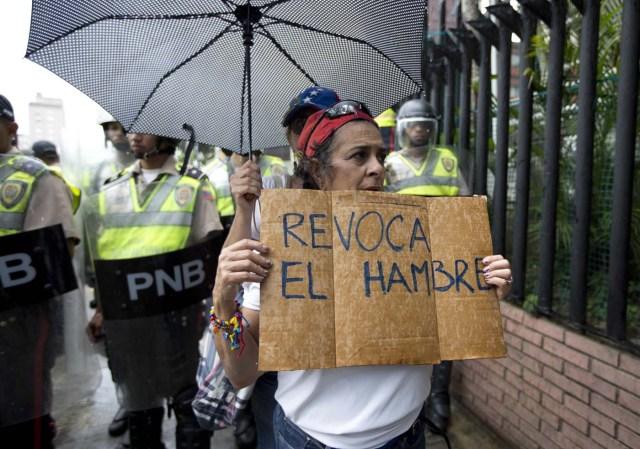 """ARCHIVO - En esta foto de archivo del 27 de julio de 2016, una mujer sostiene un letrero con el mensaje """"Revoca el hambre"""" durante una protesta en Caracas, Venezuela. La oposición venezolana superó la primera fase del proceso del referendo revocatorio del mandato del presidente Nicolás Maduro, con la validación el lunes 1 de agosto de 2016 de firmas y huellas recolectadas en junio. (AP Foto/Ariana Cubillos, Archivo)"""