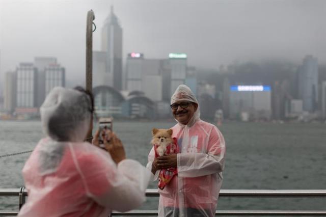 Un hombre posa para una foto con su mascota en el puerto Victoria afectado por los fuertes vientos del tifón Nida hoy, martes 2 de agosto de 2016, en Hong Kong (China). Nida es el primer gran tifón que golpea Hong Kong este año. EFE/JEROME FAVRE