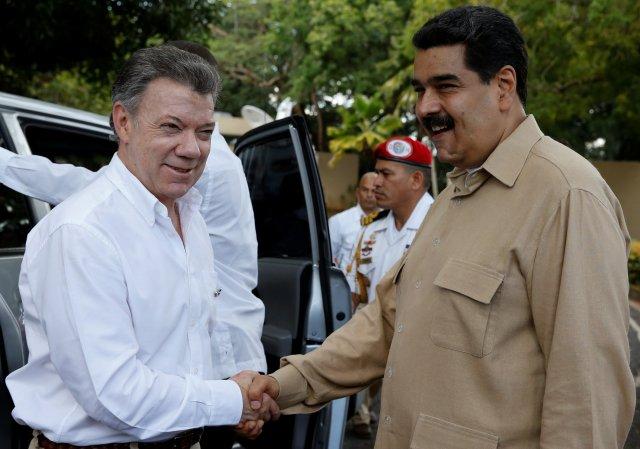 Venezuela's President Nicolas Maduro (R) and Colombia's President Juan Manuel Santos shake hands during their meeting at Macagua Hydroelectric compound in Puerto Ordaz, Venezuela, August 11, 2016. REUTERS/Carlos Garcia Rawlins