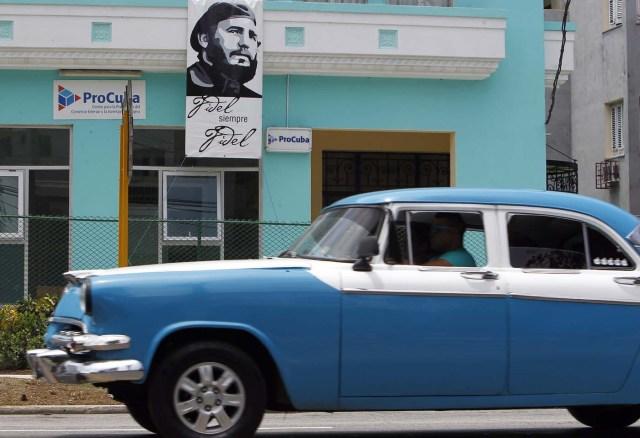 HAB116. LA HABANA (CUBA), 12/08/2016.- Un vehículo pasa hoy, viernes 12 de agosto del 2016, junto a un cartel del líder de la revolución cubana Fidel Castro, en La Habana (Cuba). Fidel Castro cumple 90 años y aunque la fecha exacta es el 13 de agosto, Cuba lleva ya meses celebrando este hito con homenajes como la composición de una sinfonía, una página web, la apertura de lugares de interés histórico e incluso una peregrinación en bicicleta hasta el pueblo natal del expresidente. EFE/Ernesto Mastrascusa