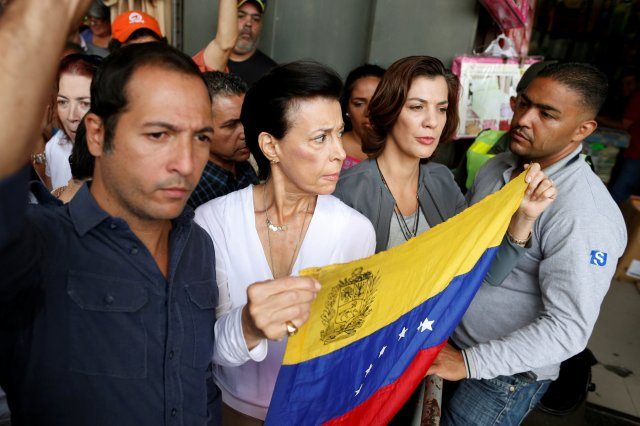 Antonieta Mendoza (C), mother of jailed Venezuelan opposition leader Leopoldo Lopez, holds a Venezuelan national flag while she waits to enter a courthouse for his hearing in Caracas, Venezuela August 18, 2016. REUTERS/Carlos Garcia Rawlins