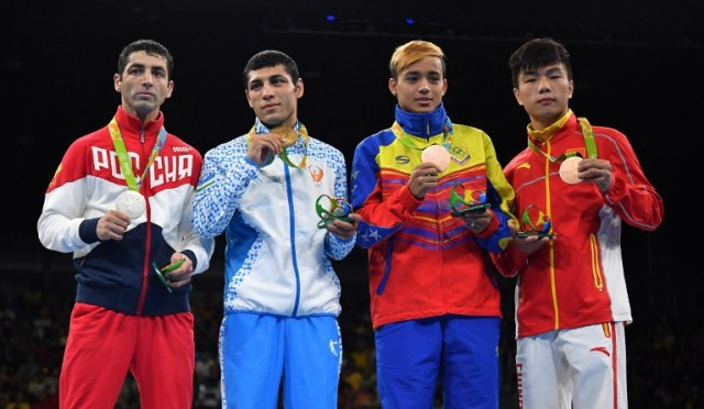 Gold medalist Uzbekistan's Shakhobidin Zoirov (2L), silver mealist Russia's Misha Aloian (L), and bronze medalists China's Hu Jianguan (R) and Venezuela's Yoel Segundo Finol react during the medal presentation ceremony following the Men's Fly (52kg) Final Bout at the Rio 2016 Olympic Games at the Riocentro - Pavilion 6 in Rio de Janeiro on August 21, 2016. / AFP PHOTO / Yuri CORTEZ