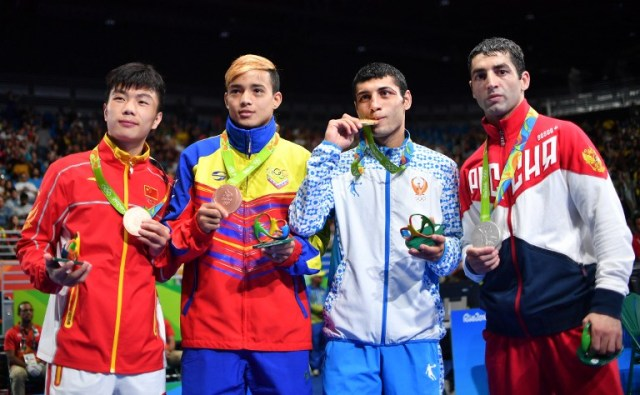 Gold medalist Uzbekistan's Shakhobidin Zoirov (2R), silver medalist Russia's Misha Aloian (R), and bronze medalists China's Hu Jianguan (L) and Venezuela's Yoel Segundo Finol react during the medal presentation ceremony following the Men's Fly (52kg) Final Bout at the Rio 2016 Olympic Games at the Riocentro - Pavilion 6 in Rio de Janeiro on August 21, 2016. / AFP PHOTO / Yuri CORTEZ