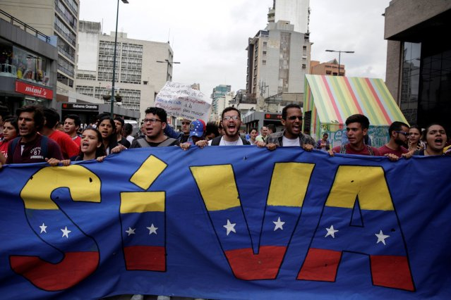 """Student demonstrators hold a banner that partially reads """"Will happen"""" while protesting against Venezuelan President Nicolas Maduro's government in Caracas, Venezuela August 24, 2016. REUTERS/Marco Bello"""