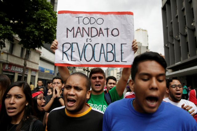 """A student demonstrator holds a sign that reads """"All mandates are revocable"""" during a gathering to protest against Venezuelan President Nicolas Maduro's government in Caracas, Venezuela August 24, 2016. REUTERS/Marco Bello"""