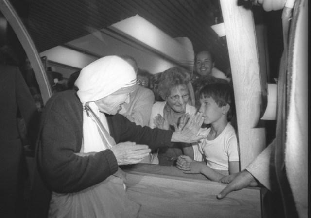 """Foto de archivo de la Madre Teresa de Calcuta saludando a un niño que estaba entre los cientos de personas que fueron a recibirla en el Aeropuerto de Quebec, Canadá. 10 de junio de 1986. La canonización de la Madre Teresa de Calcuta el domingo será la culminación de un proceso -a veces llamado """"la máquina de hacer santos""""- que es largo, complejo, caro, poco claro y con frecuencia polémico. Reuters/Jacques Boissinot"""