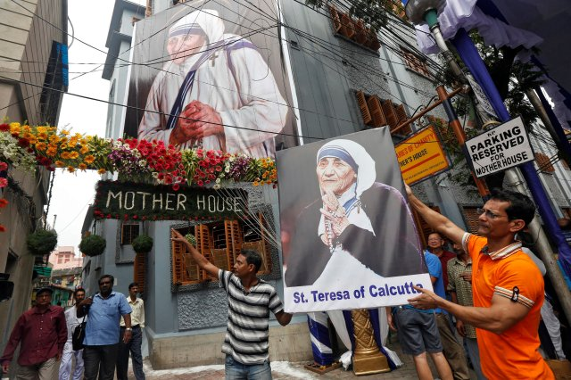 A man holds a poster of Mother Teresa outside the  Missionaries of Charity building in Kolkata as she was canonised during a ceremony held in the Vatican, India September 4, 2016. REUTERS/Rupak De Chowdhuri     TPX IMAGES OF THE DAY