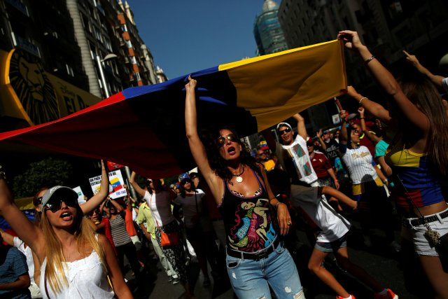 Protesters hold a Venezuelan flag during a demonstration to demand a referendum to remove Venezuela's President Nicolas Maduro, in Madrid, Spain September 4, 2016. REUTERS/Susana Vera