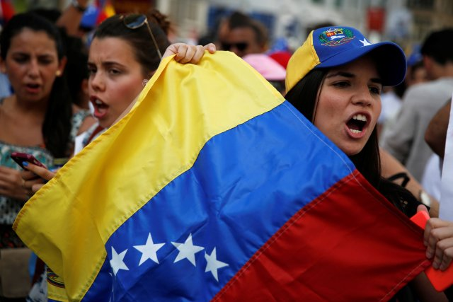 Protesters hold a Venezuelan flag during a demonstration to demand a referendum to remove Venezuela's President Nicolas Maduro, in Madrid, Spain, September 4, 2016. REUTERS/Susana Vera