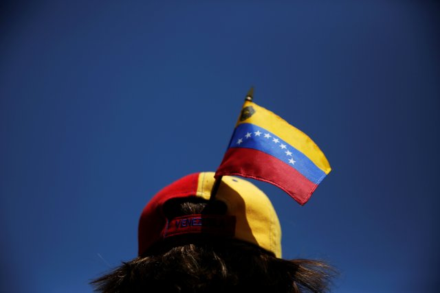 A protester carries a Venezuelan flag on her cap during a demonstration to demand a referendum to remove Venezuela's President Nicolas Maduro, in Madrid, Spain, September 4, 2016. REUTERS/Susana Vera