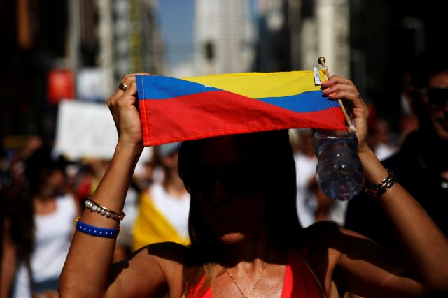 A protester shelters from the sun under a Venezuelan flag during a demonstration to demand a referendum to remove Venezuela's President Nicolas Maduro, in Madrid, Spain, September 4, 2016. REUTERS/Susana Vera