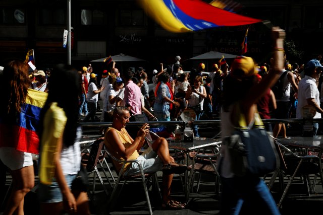 A man sits at an outdoor terrace as protesters take part in a demonstration to demand a referendum to remove Venezuela's President Nicolas Maduro, in Madrid, Spain, September 4, 2016. REUTERS/Susana Vera
