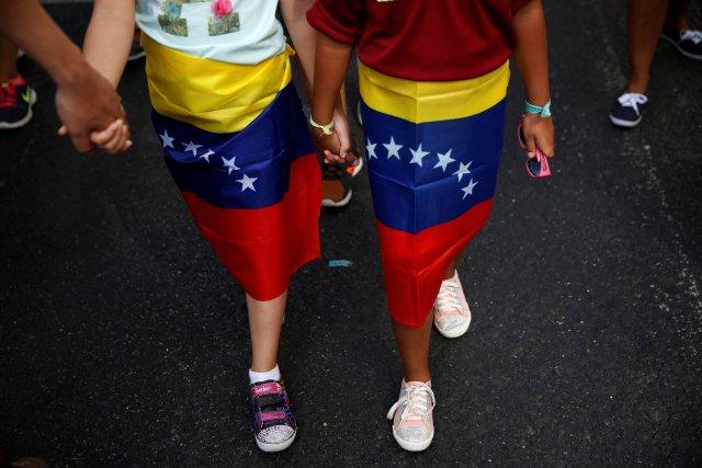 Girls wear Venezuelan flags around their waists during a demonstration to demand a referendum to remove Venezuela's President Nicolas Maduro, in Madrid, Spain, September 4, 2016. REUTERS/Susana Vera