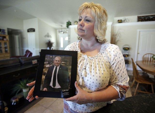 Laurie Holt sostiene una fotografía de su hijo Josh Holt, en su casa en Riverton, Utah. La representante federal Mia Love intercederá por el hombre de Utah que ha estado encarcelado en Venezuela dos meses por cargos relacionados con armas de fuego, y exigirá su liberación. (AP Foto/Rick Bowmer, archivo)