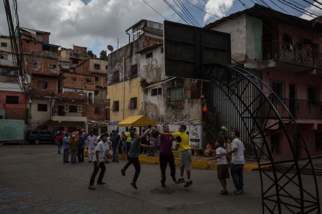 """CAR01. CARACAS (VENEZUELA), 10/09/2016.- Un grupo de personas juegan baloncesto mientras esperan por un plato de sancocho hoy, sábado 10 de septiembre del 2016, en la ciudad de Caracas (Venezuela). En el barrio la Unión, ubicado en la favela más grande de América Latina asentada en el este de Caracas, se preparó hoy un gran """"sancocho"""" como se le conoce en Venezuela a la sopa cocinada con varios tipos de verduras y carnes, para alimentar a los vecinos, muchos de ellos con varios días de hambre. EFE/MIGUEL GUTIÉRREZ"""
