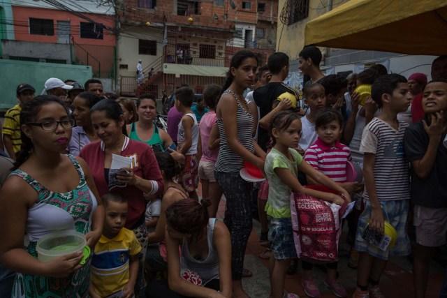 """CAR04. CARACAS (VENEZUELA), 10/09/2016.- Habitantes esperan para recibir porciones de un sancocho hoy, sábado 10 de septiembre del 2016, en la ciudad de Caracas (Venezuela). En el barrio la Unión, ubicado en la favela más grande de América Latina asentada en el este de Caracas, se preparó hoy un gran """"sancocho"""" como se le conoce en Venezuela a la sopa cocinada con varios tipos de verduras y carnes, para alimentar a los vecinos, muchos de ellos con varios días de hambre. EFE/MIGUEL GUTIÉRREZ"""