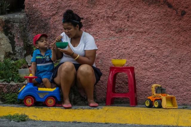 """CAR07. CARACAS (VENEZUELA), 10/09/2016.- Habitantes comen de un sancocho comunal hoy, sábado 10 de septiembre del 2016, en la ciudad de Caracas (Venezuela). En el barrio la Unión, ubicado en la favela más grande de América Latina asentada en el este de Caracas, se preparó hoy un gran """"sancocho"""" como se le conoce en Venezuela a la sopa cocinada con varios tipos de verduras y carnes, para alimentar a los vecinos, muchos de ellos con varios días de hambre. EFE/MIGUEL GUTIÉRREZ"""