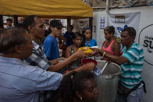 """CAR08. CARACAS (VENEZUELA), 10/09/2016.- Habitantes comen de un sancocho comunal hoy, sábado 10 de septiembre del 2016, en la ciudad de Caracas (Venezuela). En el barrio la Unión, ubicado en la favela más grande de América Latina asentada en el este de Caracas, se preparó hoy un gran """"sancocho"""" como se le conoce en Venezuela a la sopa cocinada con varios tipos de verduras y carnes, para alimentar a los vecinos, muchos de ellos con varios días de hambre. EFE/MIGUEL GUTIÉRREZ"""