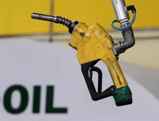 Foto de archivo: Un surtidor de combustible cuelga en una gasolinera en Seúl, 27 de junio del 2011. Una fuerte ralentización en el crecimiento global de la demanda de crudo sumado a una expansión de los inventarios y un aumento de la oferta llevarán a que el mercado tenga un excedente de oferta al menos durante los primeros seis meses del 2017, dijo el martes la Agencia Internacional de la Energía. REUTERS/Jo Yong-Hak