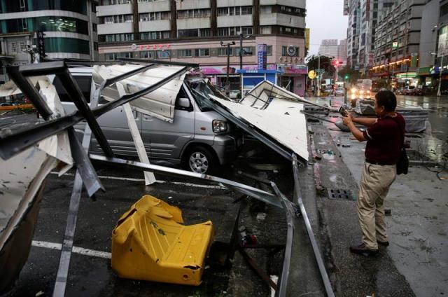 Un hombre hace fotos de un coche cubierto por planchas de metal que arrastró el viento tras el paso del supertifón Meranto por la ciudad de Kaohsiung, Taiwán. EFE
