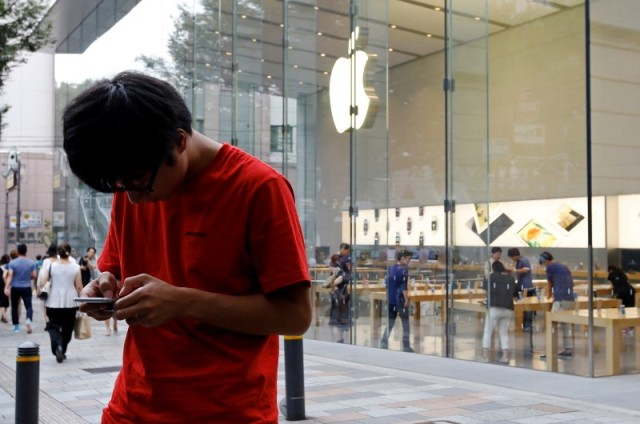 Una persona usa su iPhone 6 Plus mientras espera el lanzamiento del nuevo iPhone 7 y 7 Plus frente a una tienda Apple, en el distrito financiero Omotesando, Tokio, Japón. 15 de septiembre de 2016. Las cantidades iniciales del iPhone 7 Plus se han agotado en todo el mundo, dijo Apple la noche del miércoles, en momentos en que la compañía se prepara para llevar su nuevo dispositivo a las tiendas. REUTERS/Toru Hanai