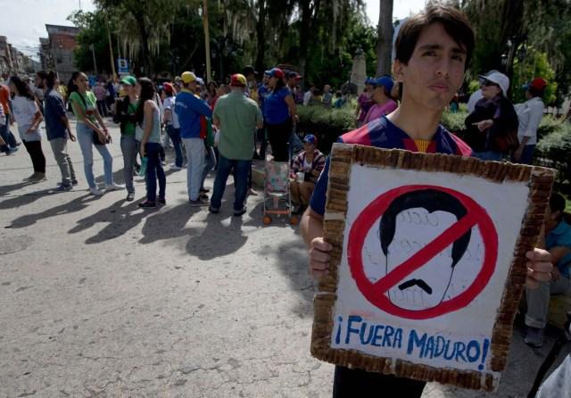 Un joven sostiene un cartel contra el presidente de Venezuela Nicolás Maduro durante una protesta en Mérida, Venezuela, el miércoles 7 de septiembre de 2016.  (AP Foto/Fernando Llano)