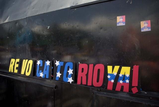 Un cartel en reclamo de la pronta realización del referendo revocatorio del mandato del presidente venezolano Nicolás Maduro es colocado por los manifestantes en la ventana de un vehículo de la policía que bloquea el acceso al Consejo Nacional Electoral en Mérida, Venezuela, el miércoles 7 de septiembre de 2016. (AP Foto/Fernando Llano)