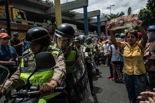 """Un manifestante en Caracas llevó a cabo un cartel diseñado para parecerse a un billete de 100 bolívares, con """"hambre"""" escrito en él en español, ya que la policía intentó disolver una manifestación en junio. MERIDITH KOHUT PARA THE NEW YORK TIMES"""