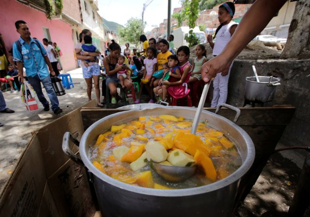 A volunteer prepares food to be distributed for free among residents on a street in the low-income neighborhood of Caucaguita near Caracas, Venezuela September 17, 2016. REUTERS/Henry Romero