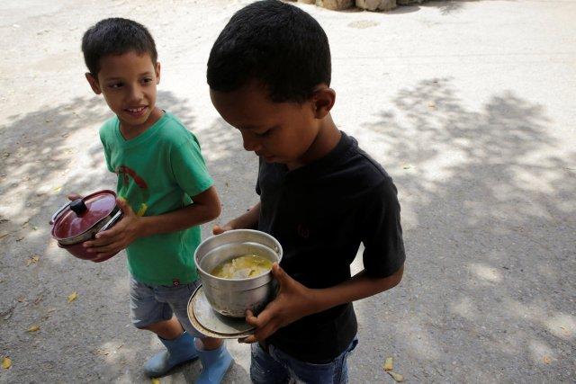 Los chicos reciben comida gratis que fue preparada por residentes y voluntarios en una calle del barrio de bajos ingresos de Caucaguita en Caracas, Venezuela 17 de septiembre de 2016. REUTERS / Henry Romero