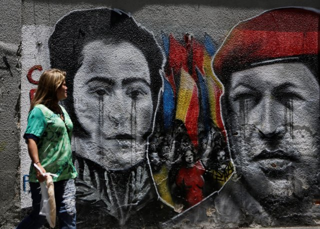 A woman looks at a mural depicting Venezuela's national hero Simon Bolivar (L) and Venezuela's late president Hugo Chavez in downtown Caracas, Venezuela September 18, 2016. REUTERS/Henry Romero FOR EDITORIAL USE ONLY. NO RESALES. NO ARCHIVES.