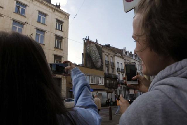 GRA227. BRUSELAS, 23/09/2016.- Dos personas fotografían uno de los grafitis de alto contenido sexual que han aparecido esta semana en Bruselas, entre las que se encuentran un falo circuncidado, la imagen de una penetración, y una vagina en pleno acto de masturbación, que han desbancado al Manneken Pis como el sexo desnudo más célebre de la ciudad. Se desconoce si las obras, que emergen en tan solo una noche, son creadas por un colectivo o por una sola persona, pero una de ellas, la del pene de seis metros de alto y tres de ancho plantada en la comuna de Saint-Gilles, será retirada después de que así lo decidieran los ediles y el propietario del inmueble. Sin embargo, los concejales del distrito centro han acordado mantener intactas las dos obras anónimas y con sesgo femenino que están sometidas a su jurisdicción. EFE/Javier Albisu