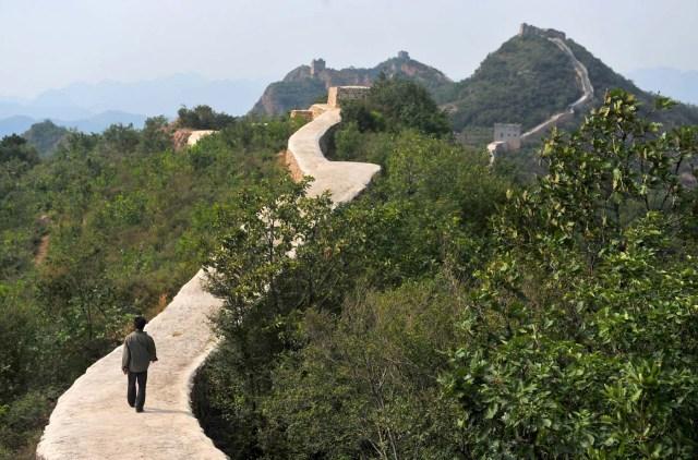 Esta foto tomada el miércoles 21 de septiembre del 2016 muestra a una persona caminando por una sección restaurada de la Gran Muralla China en el condado de Suizhong, en la provincia de Liaoning, en China. Funcionarios chinos están siendo escarnecidos por la remodelación de una sección muy apreciada de la Gran Muralla China. Reportes indicaron que la sección fue cubierta con arena y otros materiales, protegiéndola pero haciendola ver como un sendero elevado para bicicletas situado en medio de colinas llenas de árboles. (Chinatopix via AP)