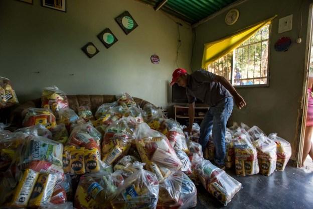ACOMPAÑA CRÓNICA: VENEZUELA ALIMENTOS - CAR01. CARACAS (VENEZUELA), 28/08/2016.- Fotografía del 20 de agosto del 2016, donde se observan un operativo de entrega de bolsas de comida a habitantes de un barrio del km 3 del Junquito por parte Comités Locales de Abastecimiento y Producción (CLAP) en Caracas (Venezuela). La severa escasez de productos básicos en Venezuela ha llevado a que la foto diaria del país sea una inmensa fila frente a muchos abastos y supermercados, un problema que el Gobierno intenta solucionar con un sistema de venta de alimentos, conformado solo por militantes chavistas, conocido como CLAP. EFE/MIGUEL GUTIÉRREZ