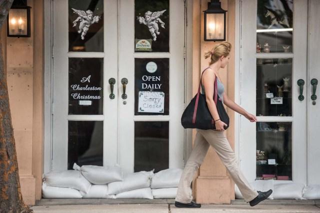 SRX01. CHARLESTON (EE.UU.), 05/10/2016.- Una mujer pasa frente a un restaurante cerrado y con bolsas de arena en las puertas hoy, miércoles 5 de octubre de 2016, como preparativos para el paso del huracán Matthew en Charleston (EE.UU.). EFE/SEAN RAYFORD