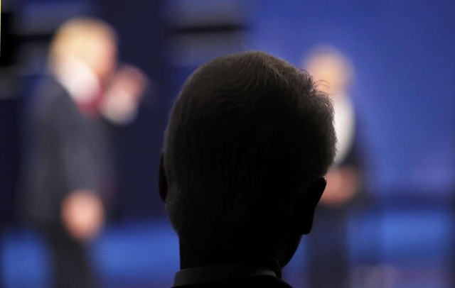 Former U.S. President Bill Clinton watches as Republican U.S. presidential nominee Donald Trump (L) and his wife, Democratic U.S. presidential nominee Hillary Clinton, participate in their presidential town hall debate at Washington University in St. Louis, Missouri, U.S., October 9, 2016. REUTERS/Shannon Stapleton
