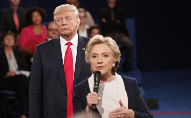 Donald Trump listens as Hillary Clinton answers a question from the audience. REUTERS/Rick Wilking